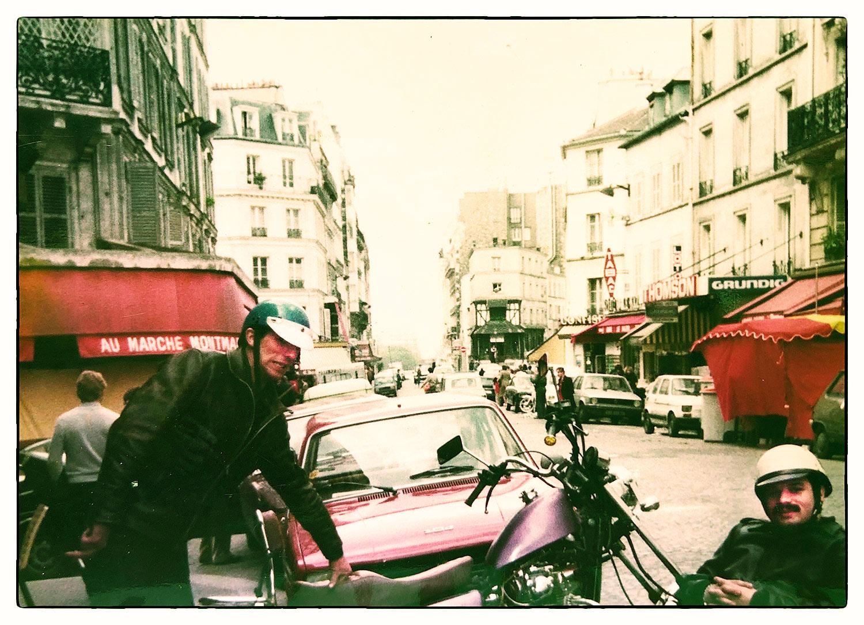 Rue des Abbesses dos à l'entrée du Café Bruant. Deux gars de la Bande avec leur moto...